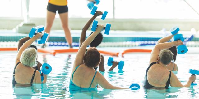Six seniors lifting weights in an aquafit class