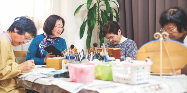 Four senior women sitting at a table doing watercolour painting